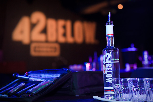 Photo of a 42Below bottle with someones bartender kit with 42Below in lights on the wall behind.
