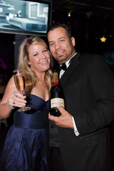 A couple dressed up holding a bottle of Moet