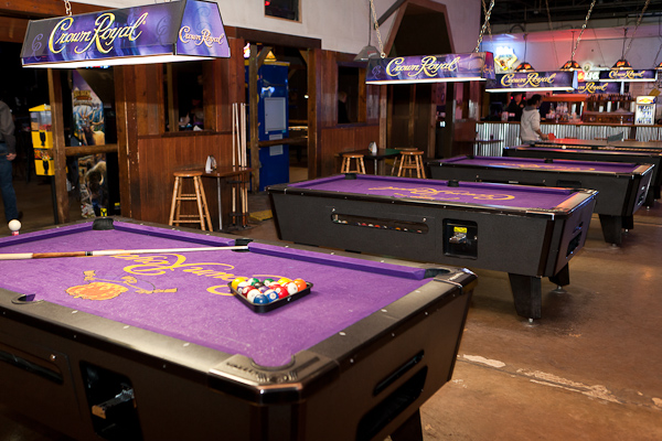 A row of pool tables all with Crown Royal felt tables and Crown Royal pool lights above them.